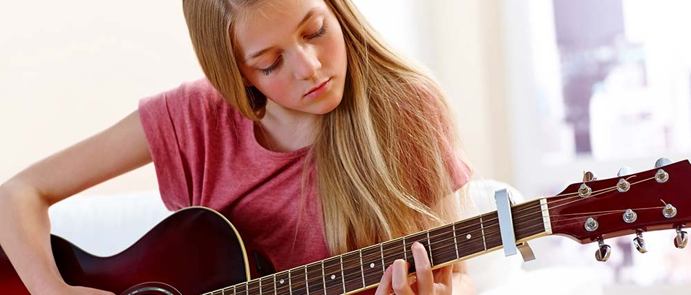 Young girl learning to play chords on the guitar