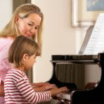 Mom playing the piano with her little girl