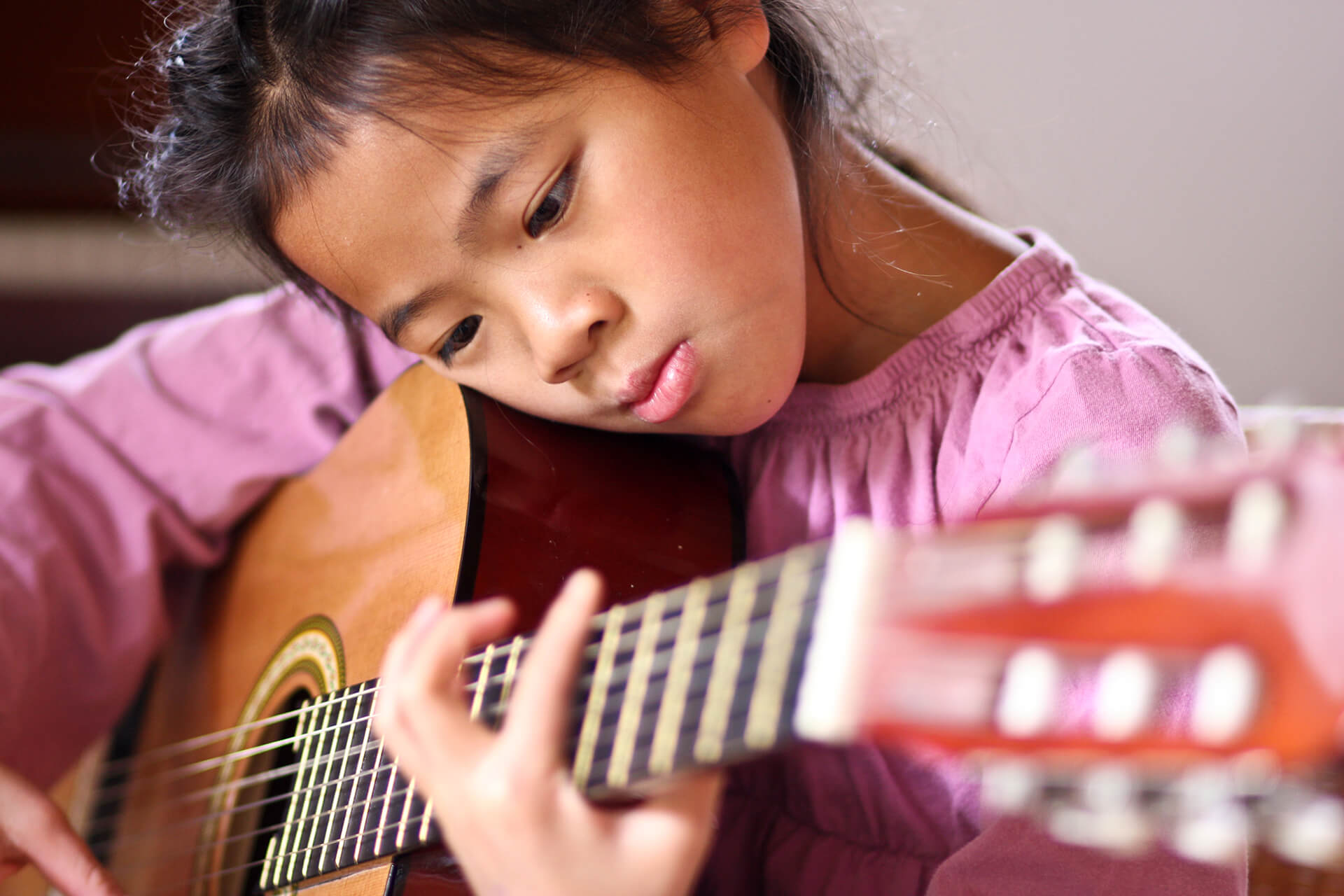 Child learning classical guitar
